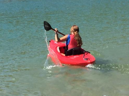 Bronwen Tedesco splashing lots of water as she speeds away in a red kayak.png
